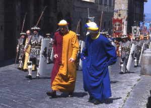 Men in medieval dress, shield and spear and long, blue, and red and orange tunics parade through an Arezzo street as part of the jousting festival.