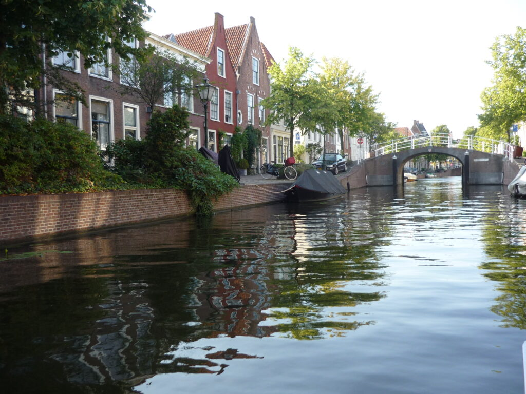 Canal with houses on one side and bridge coming up in Leiden, The Netherlands