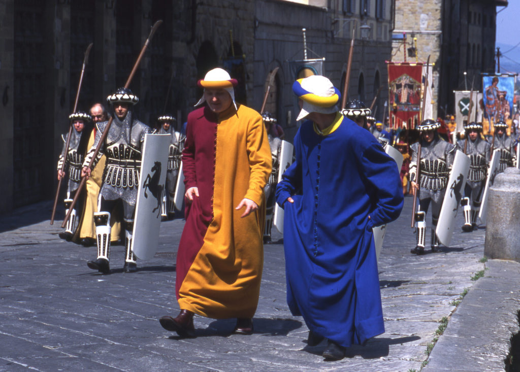 Men in red and gold and blue medieval woolen tunics accompanied by shield and spear bearing knights