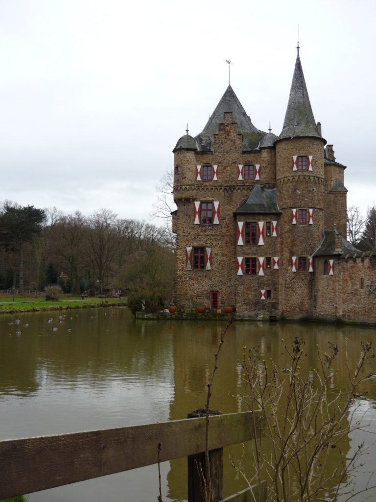 Burg Satzvey Castle with towers and moat and red and white patterned shutters. Burg Satzvey, Germany.