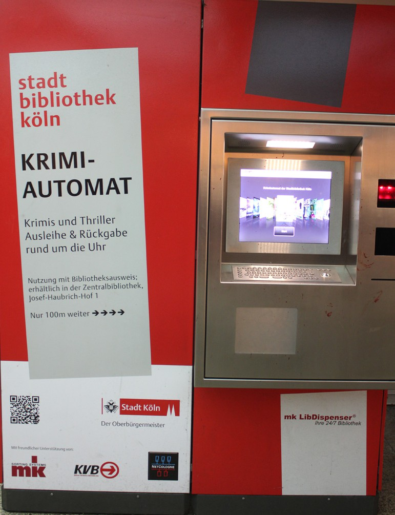 Vending machine for mystery novels from the city library in Cologne. Big red box with computer screen and door with window to get book.