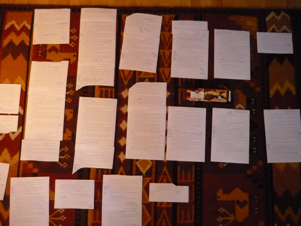 Printed papers cut in all different sizes and laid out in order on a colorful carpet. With a box of chocolate cookies for motivation.