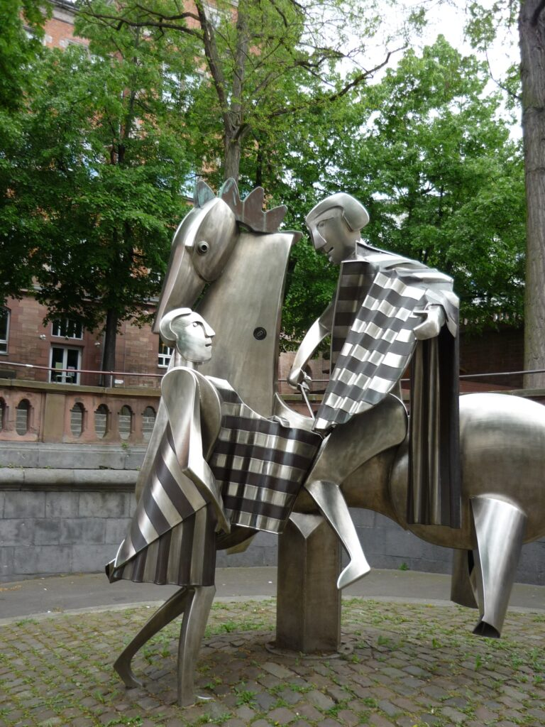 Metal sculpture of modernistic man on horseback dividing his patterned metal cloak with man on the ground.