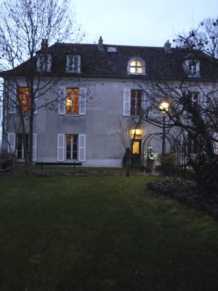 House with lit up windows as night falls in winter. Bare trees, green grass, pale blue sky.