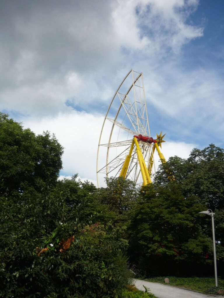 A partially constructed ferris wheel against a blue sky with puffy white clouds.