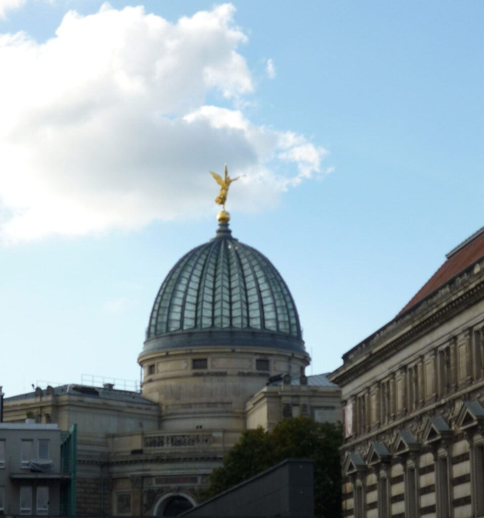 Building with glass dome with gold figure on top
