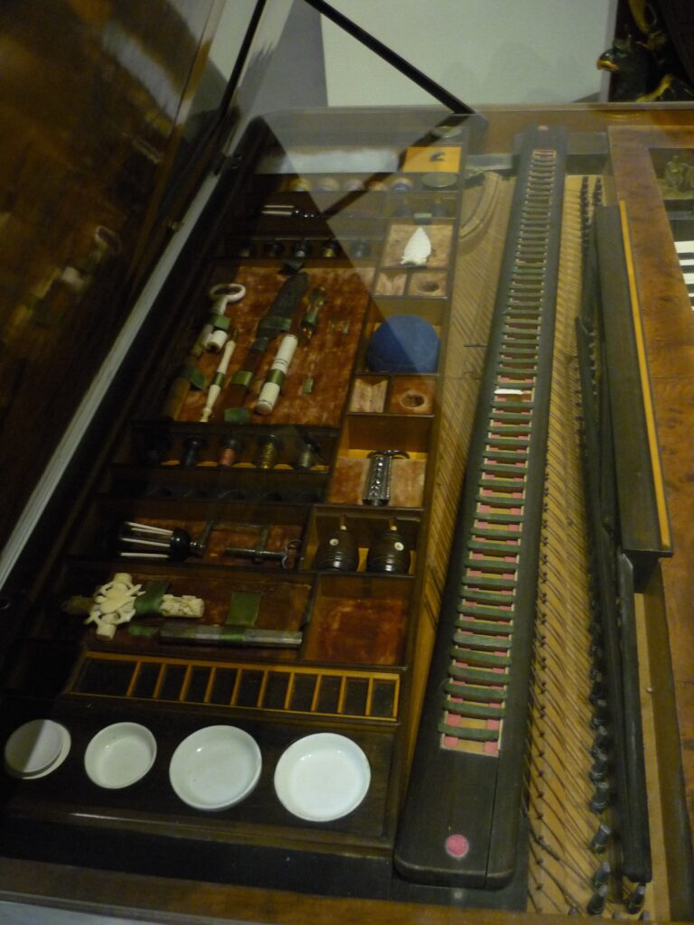 photo of compartments under the lid of a piano, paintboxes, brushes, sewing things