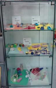 glass case with small toys and points required to earn them
