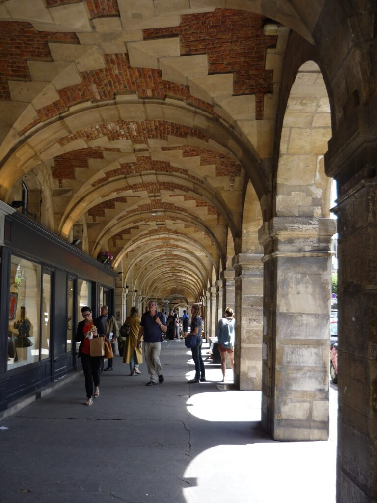 Brick and stone arcade with shops in Paris.