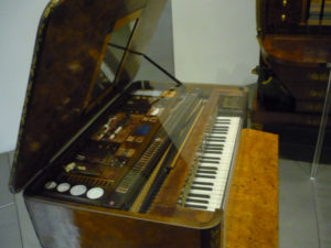 piano with open lid revealing grooming utensils underneath