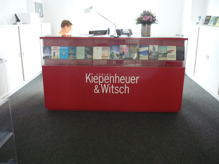 bright red front desk with name of publisher in white and a row of books in a built in shelf