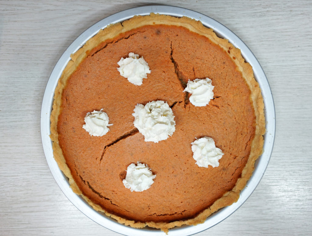 Homemade pumpkin pie with puffs of whipped cream