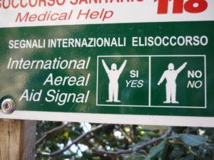Emergency sign showing body language for Si (yes) and No on a hiking trail in Italy's Cinque Terra.