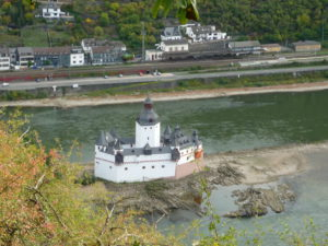 Kaub castle is red and white plaster with gray turrets. It stands on an island in the middle of the Rhine River