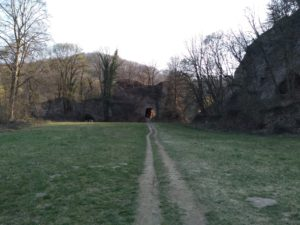 straight road to a stone cave with light shining through