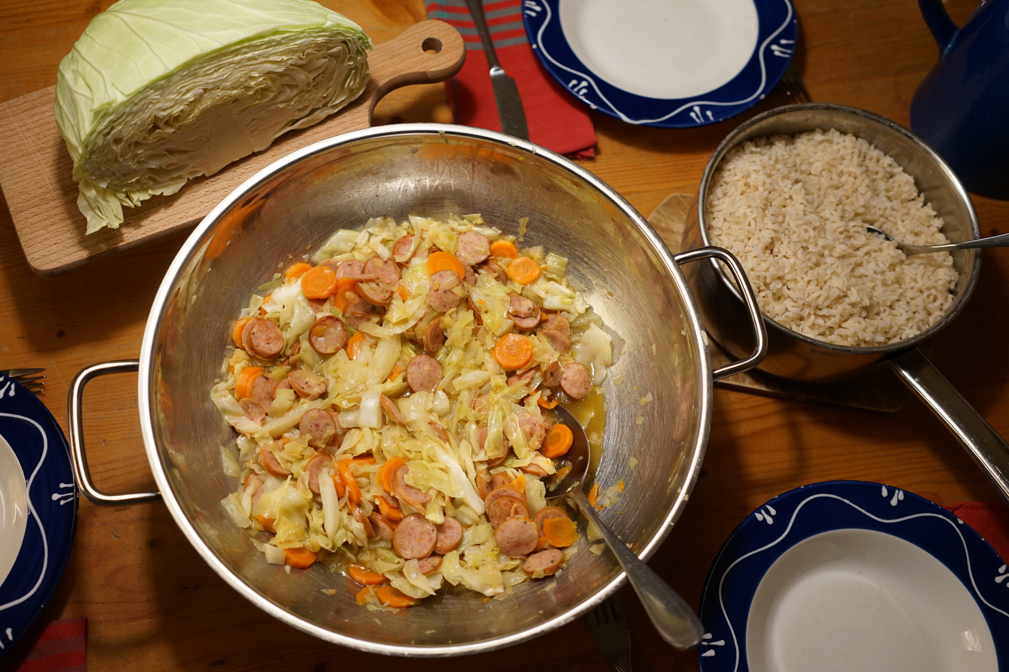 wok with sliced cabbage, carrots and kielbasa sausage next to a pot of brown rice and a flat variety cabbage cut in half