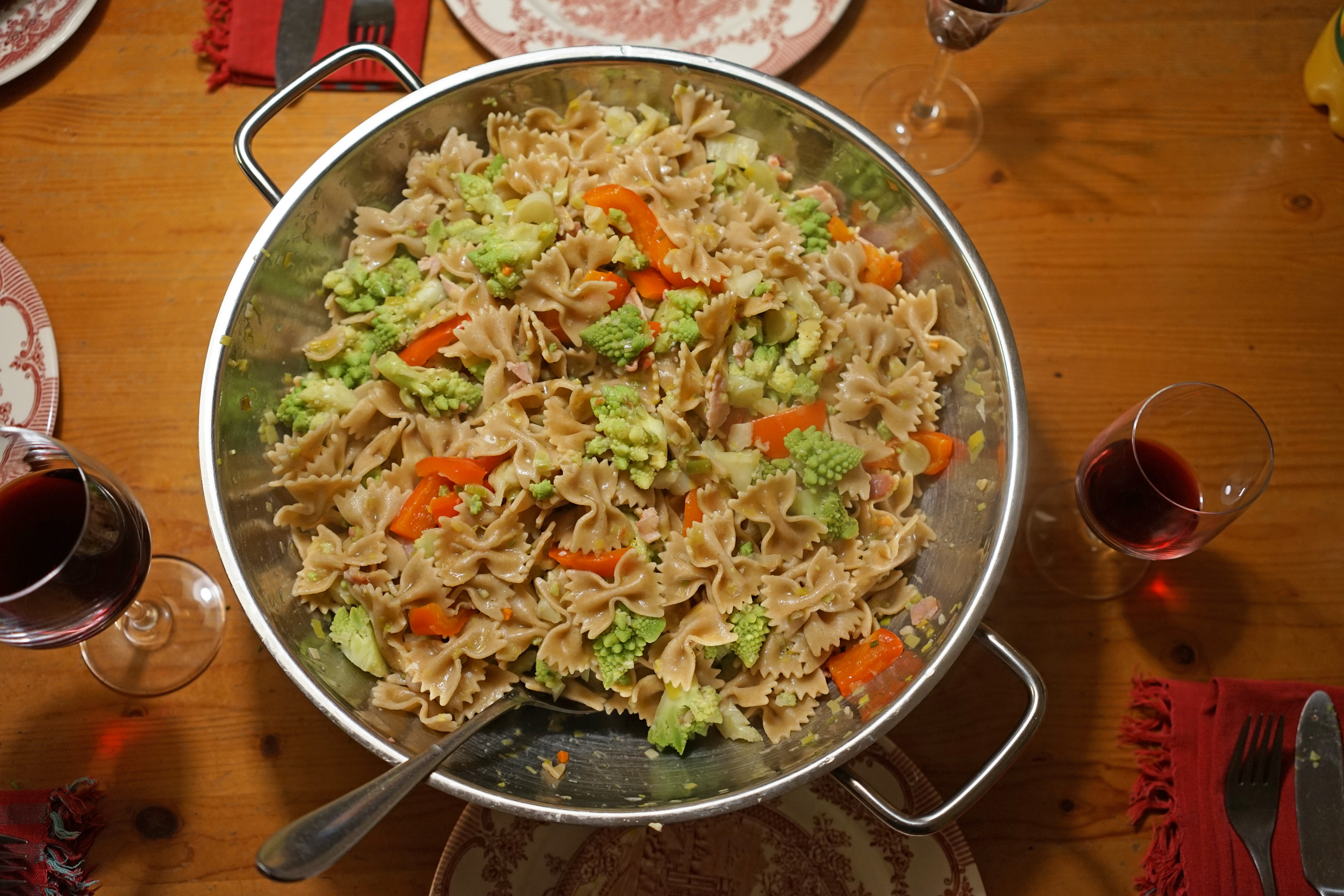 metal wok on table with butterfly pasta, red peppers, romanesco cauliflower that looks like tiny green Christmas trees