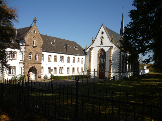 Abbey and church buildings painted white with red trim against a blue sky