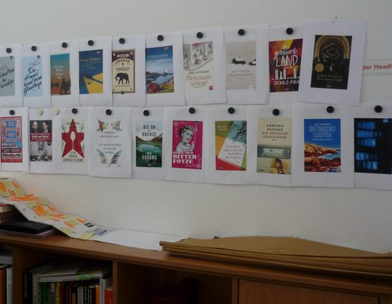 paper printouts of final bookcover designs, put up with fat round magnets