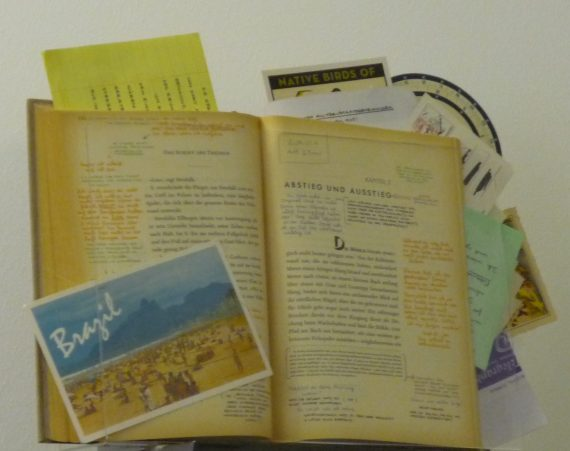 Printed book with marginal notes in two ink colors and formatted handwritten lists, postcards and other papers tucked in strategically.