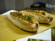 baked boats of bread filled with pesto, tomato sauce and mozzarella.
