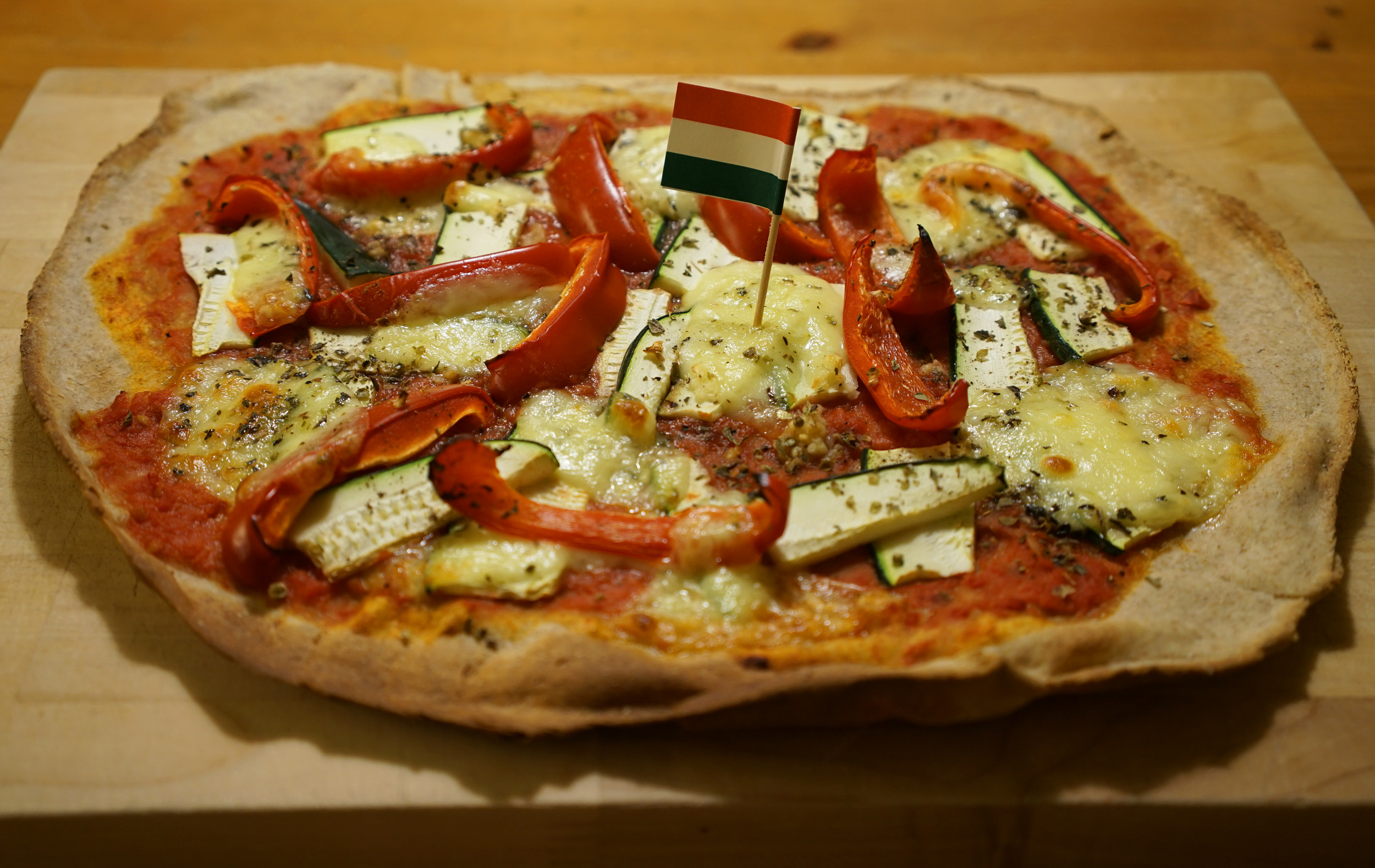 pizza baked on a stone with pepper and zucchini length-wise slices, mozzarella cheese, tomato sauce and an Italian flag toothpick in the center.