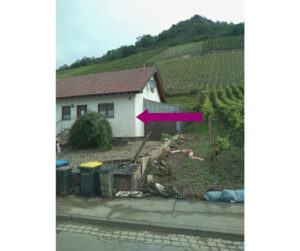 house below vineyards with water line from flooding under the front window